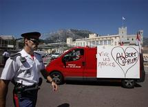 "<p>A carabinier of Prince Albert II of Monaco walks past a van with a poster reading ""Albert-Charlene, long live the newly-weds"" in front of Monaco palace as preparations continue for the upcoming wedding, June 27, 2011. REUTERS/Eric Gaillard</p>"