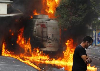 A protester walks away from a burning van during violent protests in Athens' Syntagma square, June 29, 2011. REUTERS/Yannis Behrakis