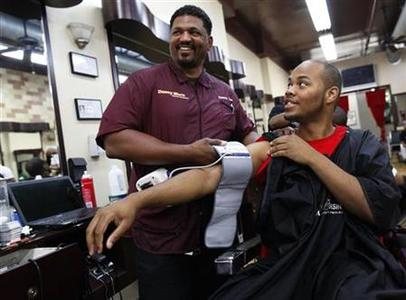 Barber Dennis ''Denny Moe'' Mitchell, 45, applies the cuff of an electronic blood pressure machine to Terrell Mack after his haircut at Denny Moe's Superstar Barbershop in New York June 8, 2011. REUTERS/Shannon Stapleton