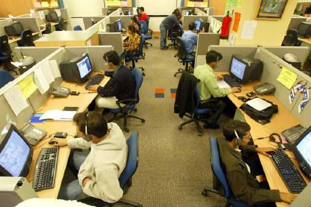 Engineers attend to calls from abroad inside a call center inGurgaon December 3,2003. REUTERS/Kamal Kishore/Files