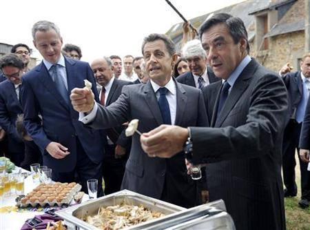 France's President Nicolas Sarkozy (C), Prime Minister Francois Fillon (R) and Agriculture, Food, Fisheries and Land Management Minister Bruno Le Maire give chicken to journalists as they visit a poultry farm in Sable-sur-Sarthe June 28, 2011. REUTERS/Eric Feferberg/Pool