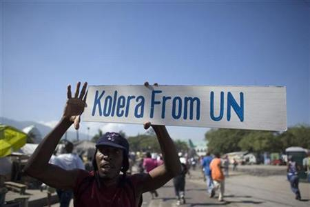 A protester holds up a sign during a demonstration against the UN mission in downtown Port-au-Prince November 18, 2010. REUTERS/Allison Shelley