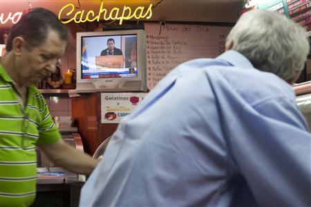 People watch Venezuelan President Hugo Chavez's televised speech in Caracas June 30, 2011. REUTERS/Carlos Garcia Rawlins