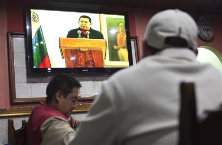 People watch Venezuelan President Hugo Chavez's televised speech at a bar in Caracas June 30, 2011. REUTERS/Carlos Garcia Rawlins
