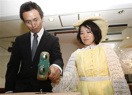 Tomoharu (L) and Miki Saito use a hammer to smash their wedding ring to symbolise the end of their 13-year marriage during their ''divorce ceremony'' in Tokyo July 3, 2011, a day before filing for divorce. REUTERS/Yuriko Nakao