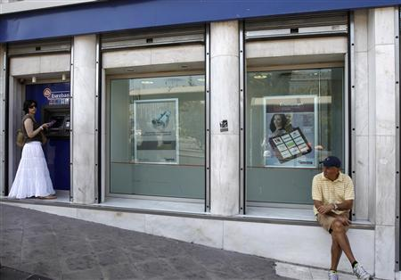 A woman makes a transaction at an automated teller machine (ATM) outside a bank branch in Athens, July 6, 2011. REUTERS/John Kolesidis