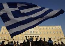 <p>Protesters raise a Greek flag in front of parliament during a rally against austerity economic measures and corruption in Athens' Syntagma (Constitution) square June 17, 2011. REUTERS/John Kolesidis</p>