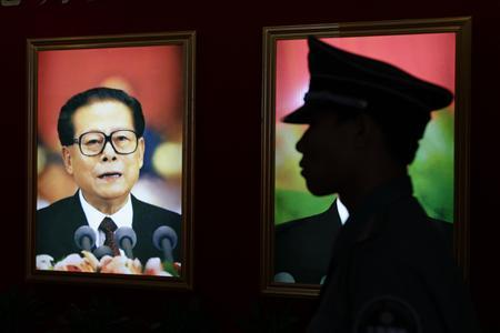 A security guard stands next to a portrait of China's former President Jiang Zemin at an exhibition to celebrate the 90th anniversary of the founding of the Communist Party of China (CPC) in Beijing July 7, 2011. REUTERS/Jason Lee