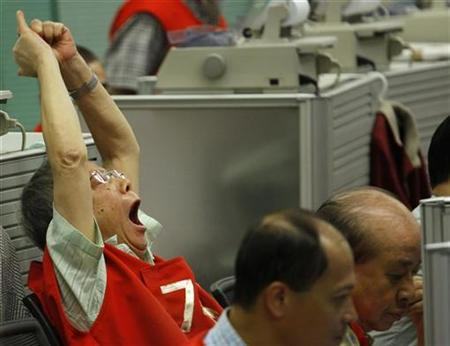 A floor trader yawns during the morning trading at the Hong Kong Stocks Exchange September 16, 2008. REUTERS/Bobby Yip