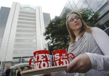 <p>News of the World employee Francine Packer brings tea and coffee to reporters waiting outside News International headquartes in London July 9, 2011. REUTERS/Luke MacGregor</p>