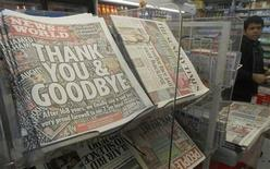 <p>Copies of the final edition of the News of the World, alongside other Sunday papers, are displayed for sale in a newsagent in London July 10, 2011. REUTERS/Luke MacGregor</p>