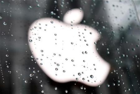 The Apple Inc. logo is seen through raindrops on a window outside of the New York City flagship Apple store in New York, January 18, 2011. REUTERS/Mike Segar