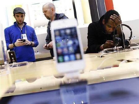 An Apple Store sales associate helps a man with an iPhone at the Apple store in New York May 23, 2011.  REUTERS/Shannon Stapleton/Files