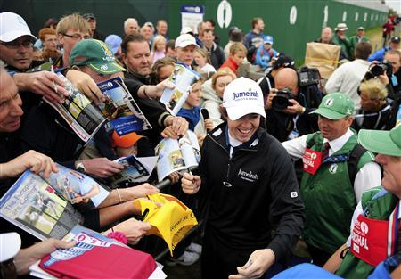 Rory McIlroy of Northern Ireland signs autographs for fans as he leaves the 18th green after the final practice round for the British Open golf championship at Royal St George's in Sandwich, southern England July 13, 2011. REUTERS/Kieran Doherty