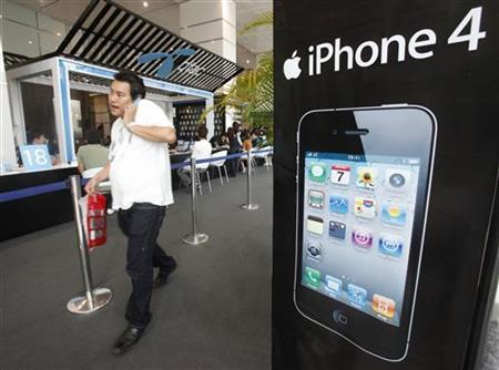 A man walks past an advertisement for an iPhone 4 displayed at a shop in Bangkok September 24, 2010. REUTERS/Chaiwat Subprasom