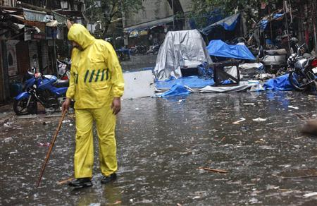 A policeman kept guard in the rain at the site of an explosion near the Opera House in Mumbai on July 14, 2011. REUTERS/Danish Siddiqui