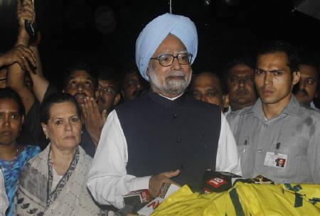 Prime Minister Manmohan Singh (C) speaks to the media as chief of India's ruling Congress party Sonia Gandhi (2nd L) watches after they met the victims of Wednesday's triple explosions at a hospital in Mumbai July 14, 2011. REUTERS/Danish Siddiqui