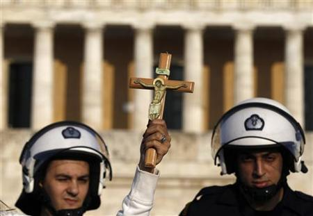 A protester holds a crucifix in front of a riot policemen during a rally at Athens' Syntagma square, March 27, 2011. REUTERS/John Kolesidis