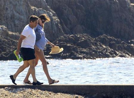 France's President Nicolas Sarkozy and his wife Carla Bruni-Sarkozy walk on a dyke before boarding a boat at the Fort de Bregancon in Bormes les Mimosas July 9, 2011. REUTERS/Jean-Paul Pelissier