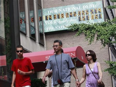 Pedestrians walk past The National Debt Clock, which displays the current United States gross national debt and each American family's share, on a wall in midtown Manhattan, in New York July 13, 2011. REUTERS/Brendan McDermid