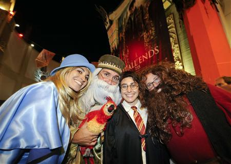 (L-R) Alicia Limon, Scott Johnson, Danny Conn and Vanessa Limon, dressed up as their favorite characters, join the crowds line up to be the first to see the new Harry Potter movie ''Harry Potter and the Deathly Hallows - Part 2'' at a minute after midnight in the Hollywood area of Los Angeles, California July 14, 2011. REUTERS/Gus Ruelas