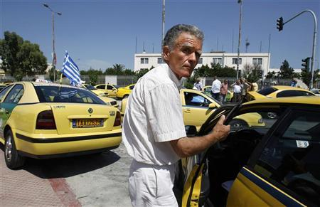 A taxi driver boards his taxi after a protest rally outside the Ministry of Transport in Athens July 6, 2011. REUTERS/Yiorgos Karahalis