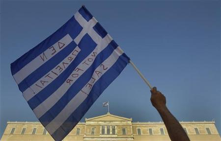 A protester waves a Greek flag during a rally in front of the parliament in Athens' Constitution (Syntagma) square June 19, 2011. REUTERS/Yiorgos Karahalis