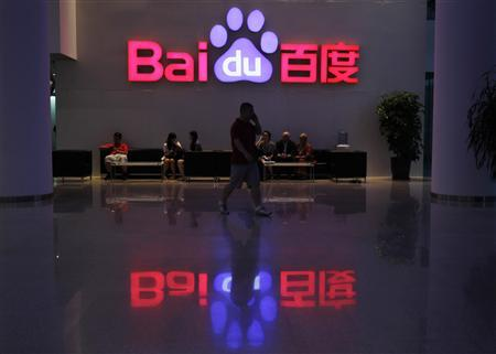 An employee uses his mobile phone as he walks past the company logo of Baidu at its headquarters in Beijing in this August 5, 2010 file photo. Baidu, China's largest search engine, signed an agreement with a joint venture owned by Universal Music, Warner Music and Sony Music to distribute songs through its mp3 search service, ending years of legal wrangling over charges that Baidu abetted piracy, according to news reports on July 19, 2011. REUTERS/Barry Huang/Files