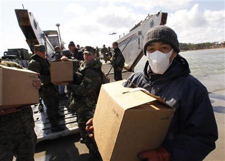 U.S. Marines and residents unload supplies for earthquake and tsunami victims from the Marines' landing craft at a port in Oshima island, northern Japan, March 27, 2011. REUTERS/Kim Kyung-Hoon