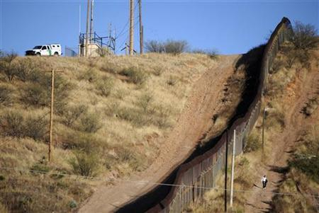 A woman walks near the border fence between Mexico and the United States in Nogales, as a U.S. border patrol vehicle is parked on the U.S. side of the border January 7, 2011. REUTERS/Alonso Castillo