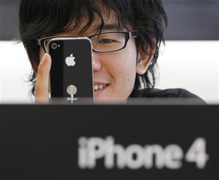 A customer tries out the iPhone 4 at Apple Inc's store in the Ginza district of Tokyo June 24, 2010. REUTERS/Yuriko Nakao