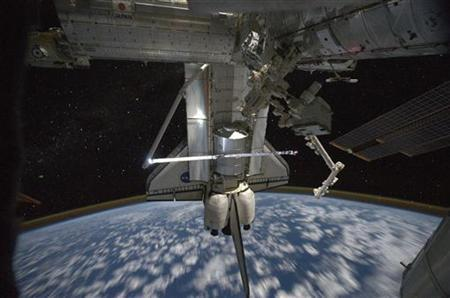 Space shuttle Atlantis is pictured while still docked with the International Space Station in this July 18, 2011 NASA handout photo taken by a crew member aboard the station. REUTERS/NASA/Handout