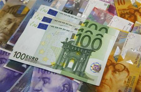 One hundred Euro banknotes lay on top of various Swiss Franc notes in this picture illustration at a bank in Warsaw, July 18, 2011. REUTERS/Kacper Pempel