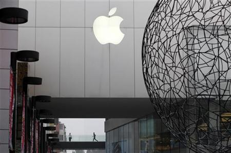 A man runs behind the building of Apple's flagship store in Beijing's Sanlitun Area, which is one of four official Apple stores in China, July 22, 2011. REUTERS/Jason Lee