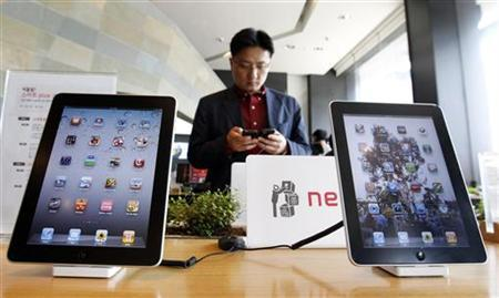 A customer holds a Apple Inc iPhone 4 smartphone on display behind the company's iPad tablets at a registration desk at the headquarters of South Korean mobile carrier KT in Seoul April 19, 2011. REUTERS/Jo Yong-Hak