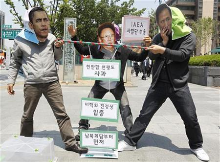 Anti-war activists wearing masks of (L to R) U.S. President Barack Obama, North Korean leader Kim Jong-il and South Korean President Lee Myung-bak take part in a rally near the U.S. embassy in Seoul May 17, 2011 to demand peace talks between the two Koreas and the restart of six party talks. U.S. special envoy on North Korea, Stephen Bosworth is on an official visit to Seoul. The green signs read (top to bottom) ''Apologise for Cheonan naval ship incident and Yeonpyeong Island attack'', ''Denuclearisation'' and ''First! Inter-Korean talk!'' The pink sign reads ''(I will) accept IAEA nuclear inspectors''. REUTERS/Jo Yong-Hak