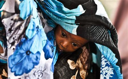A newly arrived Somali refugee carries her child as they await medical examinations at the Dadaab refugee camp, near the Kenya-Somalia border, July 23, 2011. REUTERS/Kabir Dhanji