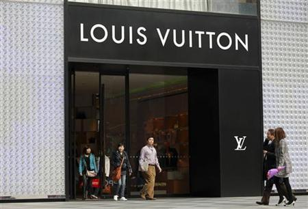 Shoppers walk past a Louis Vuitton store in Shanghai March 8, 2011. REUTERS/Aly Song