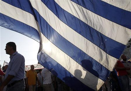 Taxi drivers stand near a huge Greek flag during a protest outside the parliament in Athens' Syntagma (Constitution) square, July 26, 2011. REUTERS/John Kolesidis