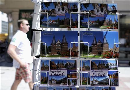 A tourist passes a rack of postcards showing famous landmark Holstentor (Holsten Gate) in downtown Luebeck, June 4, 2011. REUTERS/Fabian Bimmer
