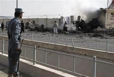 <p>An Afghan policeman (L) watches as firefighters work at the site after a car bomb explosion in Lashkar Gah, capital of Helmand province July 31, 2011. REUTERS/Abdul Malik Watanyar</p>