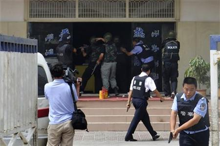 A handout picture shows armed policemen trying to rescue hostages at a police station during a clash in Hotan, Xinjiang Uygur Autonomous Region July 18, 2011. REUTERS/Xinjiang Public Security Bureau/Handout