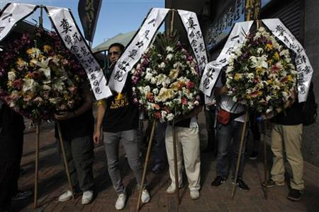 Wreaths are displayed in Hong Kong during a ceremony to remember the victims of the Wenzhou's train accident, July 31,2011. China's state news agency Xinhua has denied widespread rumours that railway authorities tried to conceal evidence by burying carriages damaged during a high-speed rail crash that killed at least 40 people last weekend. REUTERS/Tyrone Siu
