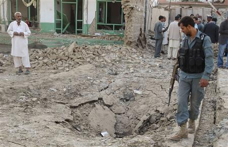 An Afghan policeman looks at a crater at a guesthouse after it was attacked by suicide bombers in Kunduz province August 2, 2011. REUTERS/Wahdat