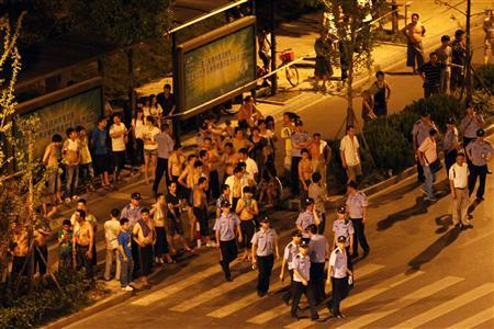 Policemen walk past a crowd gathered near the homes of taxi drivers in the suburbs of Hangzhou, Zhejiang province August 2, 2011. REUTERS/Aly Song
