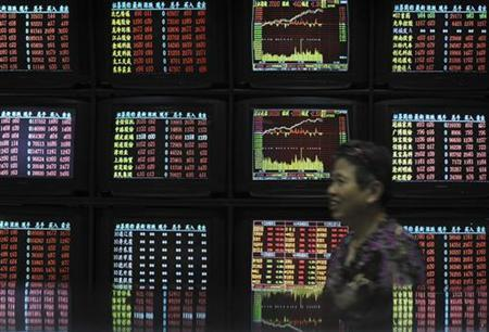 An investor smiles as she walks past screens showing stock information at a brokerage house in Wuhan, Hubei province June 24, 2011. REUTERS/China Daily
