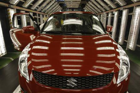 A worker checks a car on the inspection line in the Hungarian plant of Japanese car maker Suzuki in the town of Esztergom, 60 km (37 miles) west of Budapest, July 14, 2011.  REUTERS/Bernadett Szabo/Files