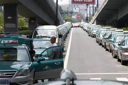 Striking taxi drivers gather near their parked taxis under a bridge in the suburbs of Hangzhou, Zhejiang province August 3, 2011. REUTERS/Aly Song