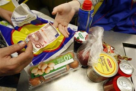 A shopper pays for food at the cash register in a discount supermarket in Nice, southern France, October 16, 2008. REUTERS/Eric Gaillard