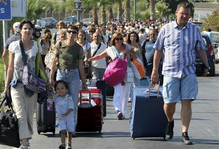 Tourists carry their luggage as they try to reach the airport in Herakleion August 1, 2011. REUTERS/Image Photo Services